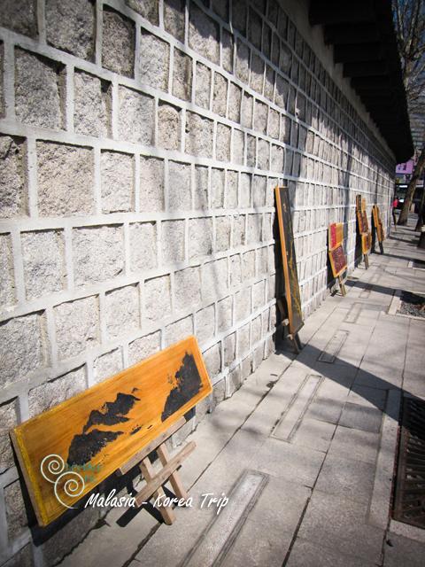 ระหว่างถ่ายรูปก็เหลือบไปเห็น ข้างกำแพงกจะมีศิลปะที่ทำจากไม้วางขายอยู่จ้า